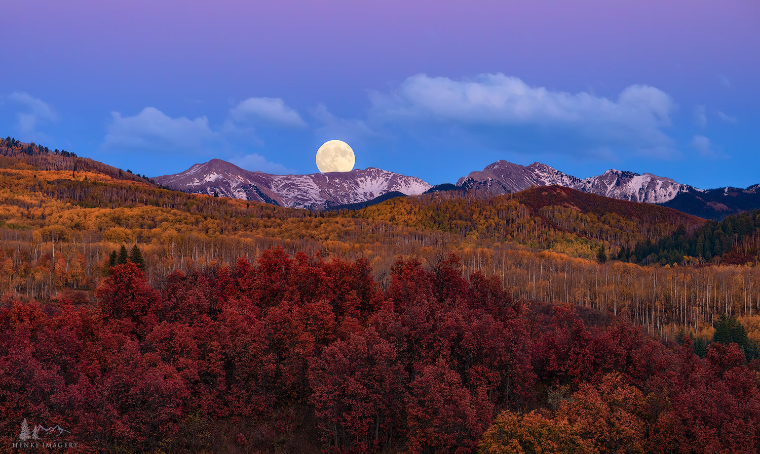 A fall harvest moon rises over the Elk Mountains in Colorado.